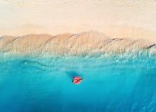 Vogelperspektive einer schwimmenden Frau im Meer bei Sonnenuntergang stockfoto