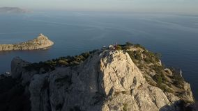 Vogelperspektive einer Stellung der jungen Frau auf die Oberseite eines Berges, der das Meer gegenüberstellt Dame auf dem Gipfel  stock video