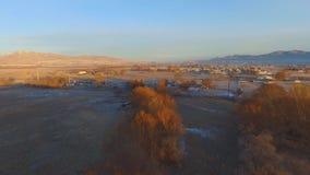 Vogelperspektive einer Waldung der Bäume, der Bauernhöfe, der Felder mit einer Stadt und der schneebedeckten Berge im Abstand stock video