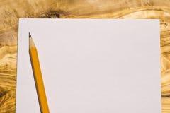Vogelperspektive eines Blattes Papier mit einem gelben Bleistift auf einem hölzernen Stockfotografie
