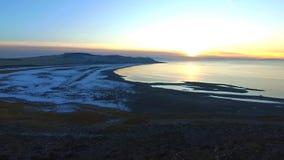Vogelperspektive eines erstaunlichen Sonnenuntergangs mit einer Küstenlinie unten entlang dem Ufer von einem großen See, von Meer stock video
