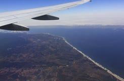 Vogelperspektive eines Flugzeugflügels über Kalifornien-Küste Stockfotografie