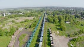 Vogelperspektive eines kleinen ländlichen Bahnhofs mit einem Güterzug stock video footage