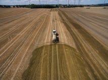Vogelperspektive eines Landwirtschaftstraktors mit einem Anhänger befruchtet ein frisch gepflogenes agriculural Feld mit Düngemit Lizenzfreie Stockbilder