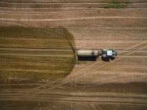 Vogelperspektive eines Landwirtschaftstraktors mit einem Anhänger befruchtet ein frisch gepflogenes agriculural Feld mit Düngemit Stockbild