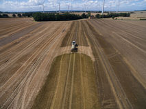 Vogelperspektive eines Landwirtschaftstraktors mit einem Anhänger befruchtet ein frisch gepflogenes agriculural Feld mit Düngemit Stockfoto