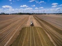 Vogelperspektive eines Landwirtschaftstraktors mit einem Anhänger befruchtet ein frisch gepflogenes agriculural Feld mit Düngemit Lizenzfreie Stockfotos