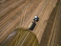 Vogelperspektive eines Landwirtschaftstraktors mit einem Anhänger befruchtet ein frisch gepflogenes agriculural Feld mit Düngemit Stockbilder