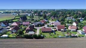 Vogelperspektive eines Neubauwohnungenzustandes mit Einzelhäusern und Gärten Am Rand eines Dorfs mit einem Feld im Vordergrund, n Lizenzfreies Stockfoto