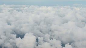 Vogelperspektive 4K über Wolken vom Flugzeugfenster mit blauem Himmel stock footage