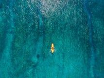 Vogelperspektive mit Surferfrau auf Surfbrett im blauen Ozean Beschneidungspfad eingeschlossen stockbild