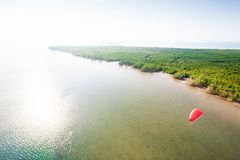 Vogelperspektive, paramotor, das über die Insel am Sonnenscheintag fliegt r lizenzfreies stockbild