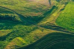 Vogelperspektive vom Brummen oder vom Luftfahrzeug im ländlichen Ackerland der Landschaft mit grünen Feldhügeln und Wiesen, Drauf Stockbilder