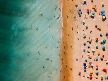 Vogelperspektive vom Fliegen-Brummen der Leute-Menge entspannend auf Algarve-Strand stockbilder