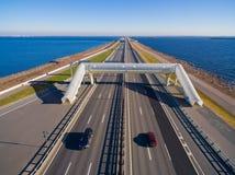 Vogelperspektive von Autobahnen mit obenliegendem Fußgängerübergang, umgeben durch Wasser Lizenzfreie Stockbilder