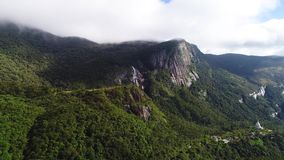 Vogelperspektive von Bergen, der Wald und Wasserfall, die mit Wolken auf Adam-` s bedeckt werden, ragen in Sri Lanka empor stock footage