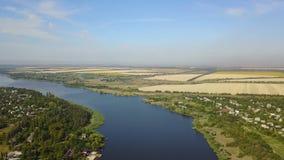 Vogelperspektive von blauem Fluss mit kleinem Dorf und von Feldern auf Banken, Brummen schoss von der ländlichen Sommerlandschaft stock footage