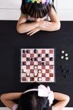 Vogelperspektive von den asiatischen chinesischen kleinen Schwestern, die Schach togeth spielen Lizenzfreies Stockfoto
