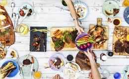 Vogelperspektive von den Händen, die zusammen Lebensmittel teilen stockfotos