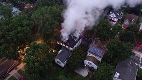 Vogelperspektive von den Löschfahrzeugen und von Apparat, die einen Hausbrand kämpfen stock footage