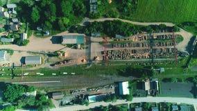 Vogelperspektive von den Lastwagen, die mit Holz gefüllt werden, reisen auf die Eisenbahnlinien nahe der Straße mit dem Autofahre stock footage