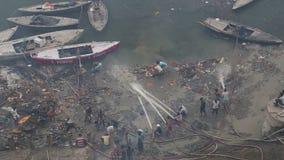 Vogelperspektive von den Männern, die schmutziges Ufer vom Ganges in Varanasi säubern stock footage