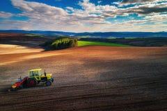 Vogelperspektive von den Traktoren, die an dem Erntefeld arbeiten Stockbilder