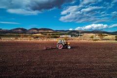 Vogelperspektive von den Traktoren, die an dem Erntefeld arbeiten Lizenzfreies Stockfoto
