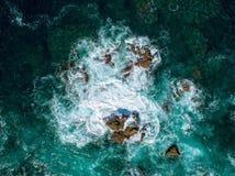Vogelperspektive von den Wellen, die auf Felsen brechen Stockfotos