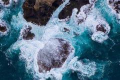 Vogelperspektive von den Wellen, die auf Felsen zusammenstoßen stockfotografie