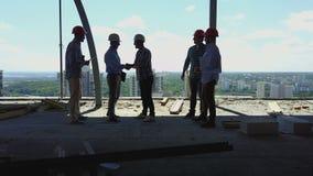 Vogelperspektive von Erbauern team Händedruck mit Geschäftsmannarbeitgeber auf Baustelle, Sitzung der Gruppe Auftragnehmer stock footage
