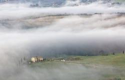 Vogelperspektive von Gipfelbauernhäusern u. von Zypressenbäumen in Toskana auf einem nebeligen Frühlingsmorgen | stockfotos