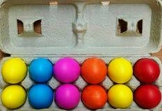 Vogelperspektive von hellen gefärbten Ostereiern in einem Karton lizenzfreie stockbilder