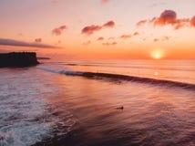 Vogelperspektive von Ozean mit Wellen, Surfern und warmem Sonnenuntergang in Bali lizenzfreie stockbilder