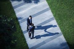 Vogelperspektive von zwei Geschäftsmännern, die Hände auf dem Bürgersteig rütteln stockbild
