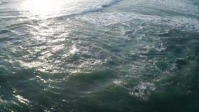 Vogelperspektivefliegen über den schönen Meereswellen, die über Felsen gegen schwarzen Sandstrand in Bali zerquetschen stock video