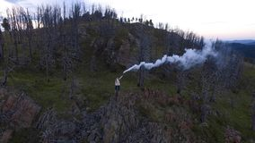 Vogelperspektivefrauenstand auf Klippe mit Rauchbombe stock footage