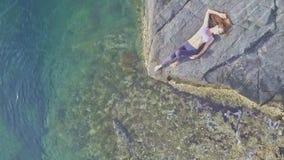 Vogelperspektivemädchen liegt auf felsigem Strand gegen Türkisozean stock footage
