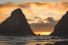 Vogels die tussen overzeese rotsstapels bij zonsondergang vliegen Royalty-vrije Stock Fotografie