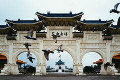 Vogels die voor Chiang Kai Shek Memorial Hall vliegen stock afbeeldingen