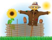 Vogelscheuchenstroh in einem Mantel und in einem Hut mit Zaun und Sonnenblumen Stockfotos