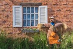 Vogelverschrikker op de muur en de vensters die met gras en bloemen wordt gevuld. Stock Fotografie