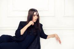 Vogue-Artporträt der schönen Brunettefrau auf einem Sofa mit lizenzfreies stockfoto