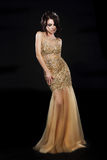 Vogue. Beautiful Fashion Model In Golden-Yellow Dress over Black. Pretty Woman In Gold - Yellow Gown on Black Background Stock Photo