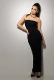 Vogue. Beautiful woman posing in black dress Stock Photo