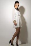 Vogue. Beautiful woman posing in white dress Stock Photo