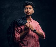 Vogue, fashion, style. Handsome young Indian guy wearing a pink shirt holding a jacket on his shoulder and looking stock photography