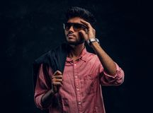 Vogue, fashion, style. Handsome young Indian guy wearing a pink shirt and sunglasses holding a jacket on his shoulder royalty free stock image