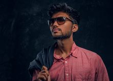 Vogue, fashion, style. Handsome young Indian guy wearing a pink shirt and sunglasses holding a jacket on his shoulder royalty free stock photo