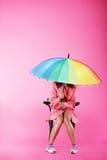 Vogue. Frau im rosa Mantel, der mit buntem Regenschirm sitzt stockfoto